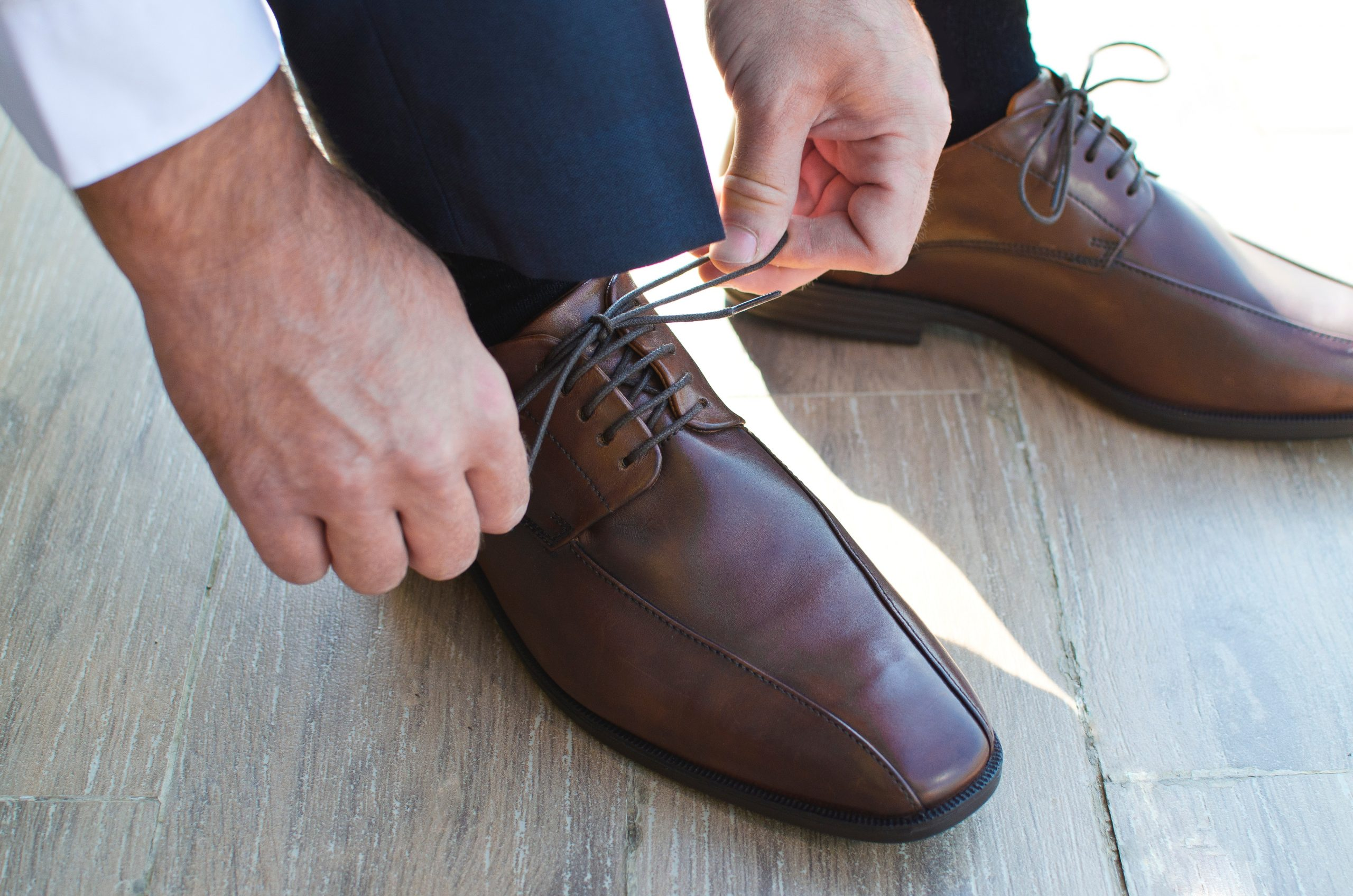 focus shot of a man tying the shoelaces of his brown leather dress shoes