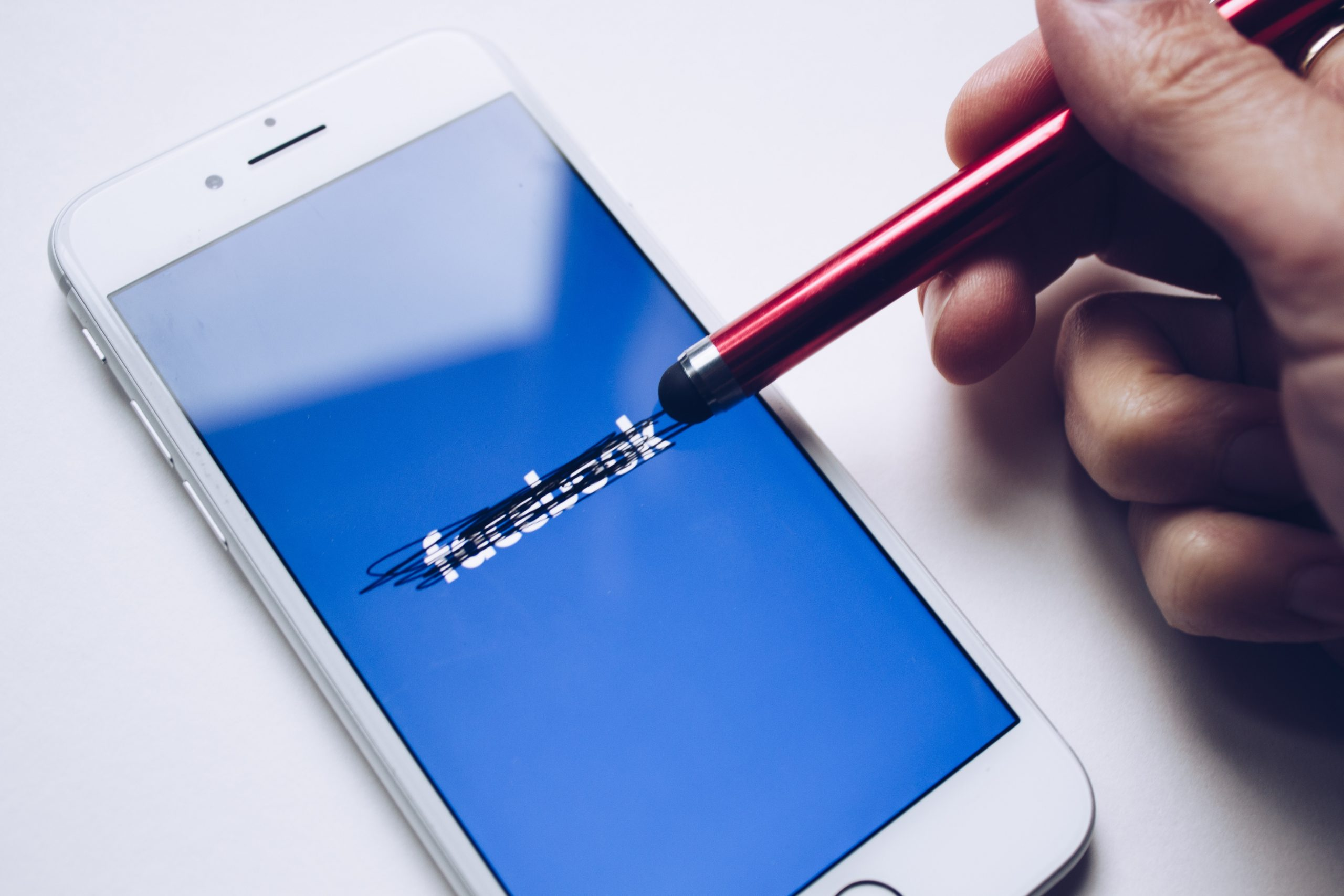 an iphone screen showing the facebook logo being cancelled out in black with a stylus pen