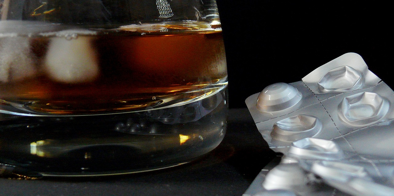 whisky glass and pill blister pack, substance addiction, drugs, alcohol, negative coping strategies