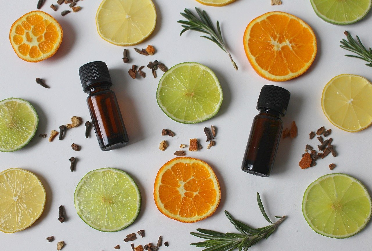 Essential oil bottles among orange and lime slices, rosemary sprigs and cloves on a white background