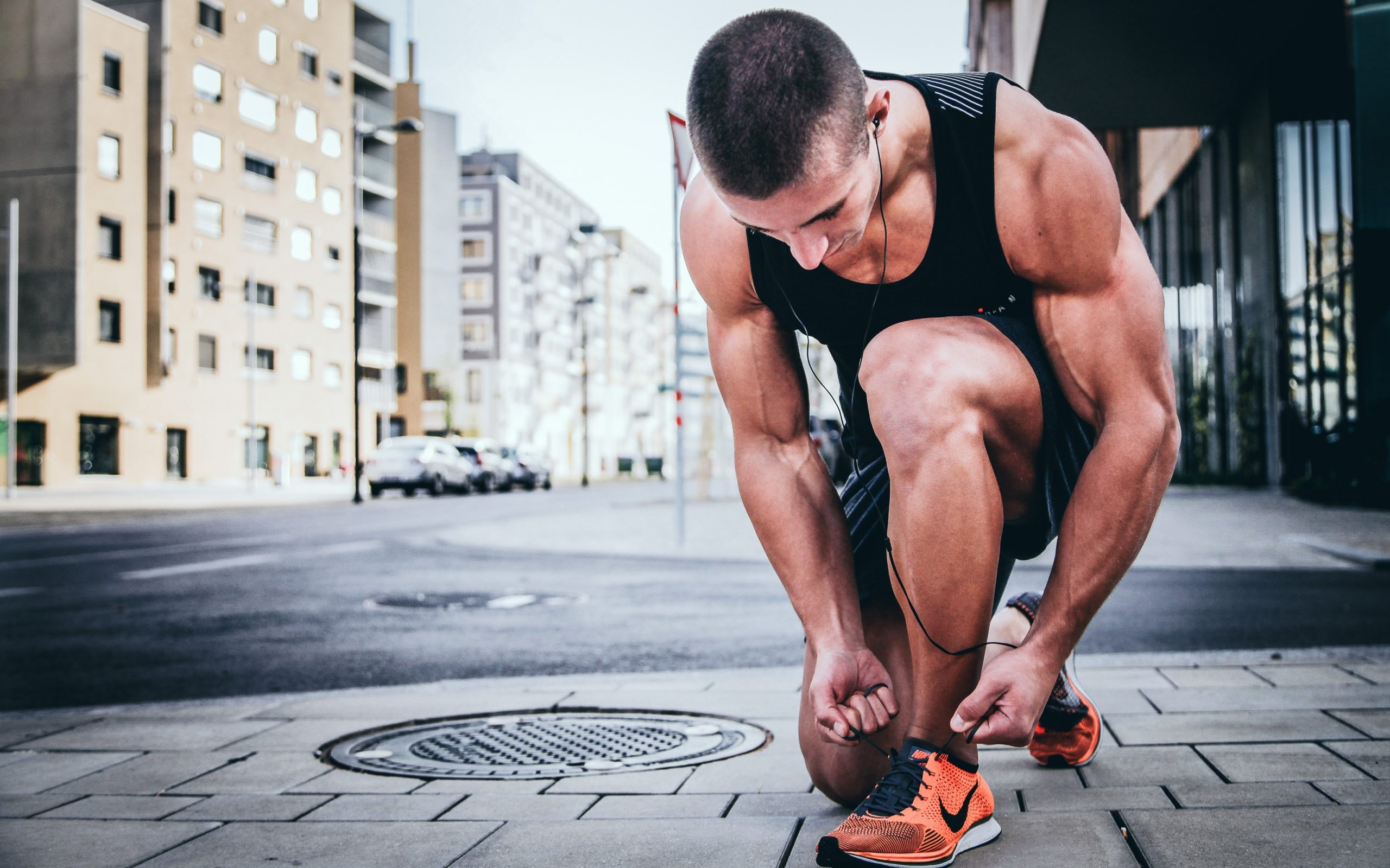 man kneeling to tie his running shoe while running in the streets