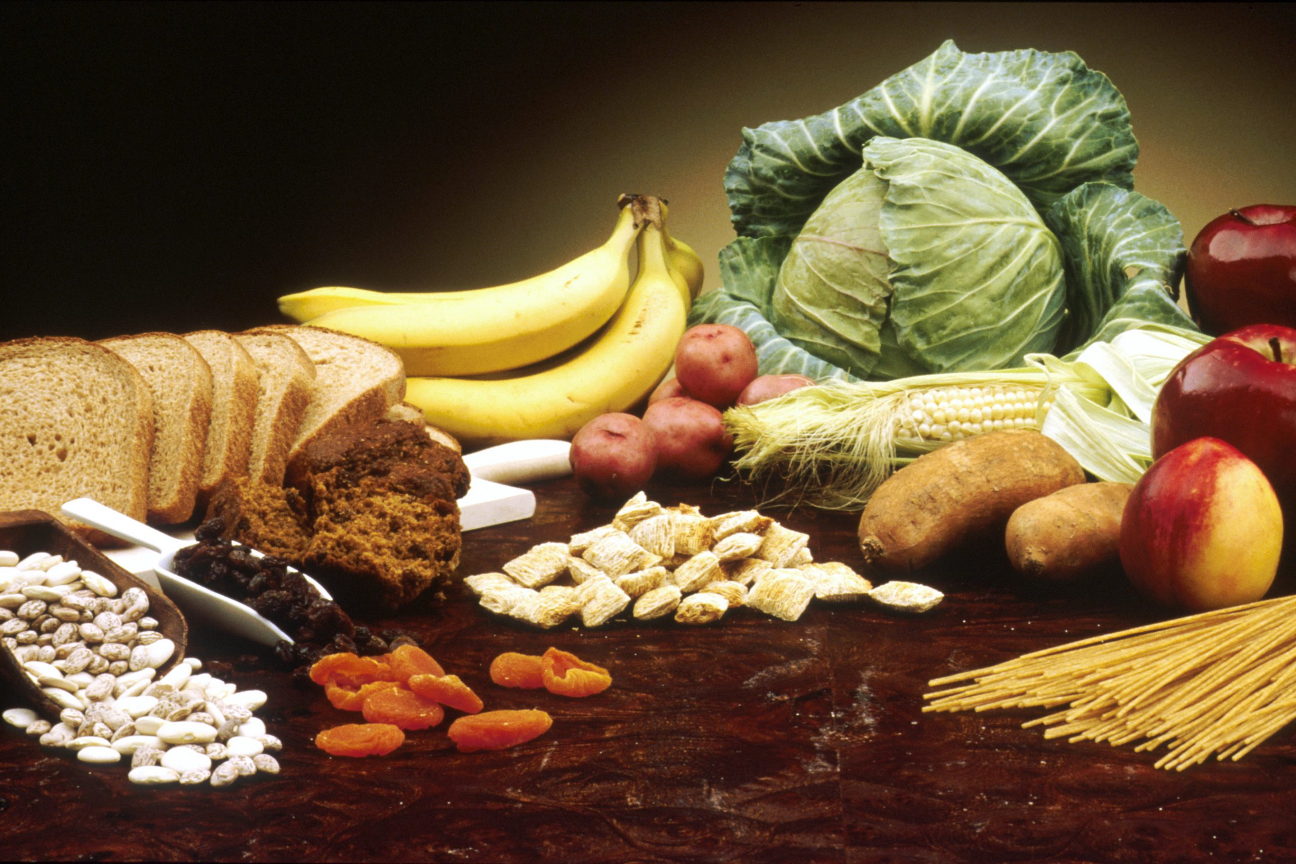 a spread of fruits, vegetables and grain products on a wooden table