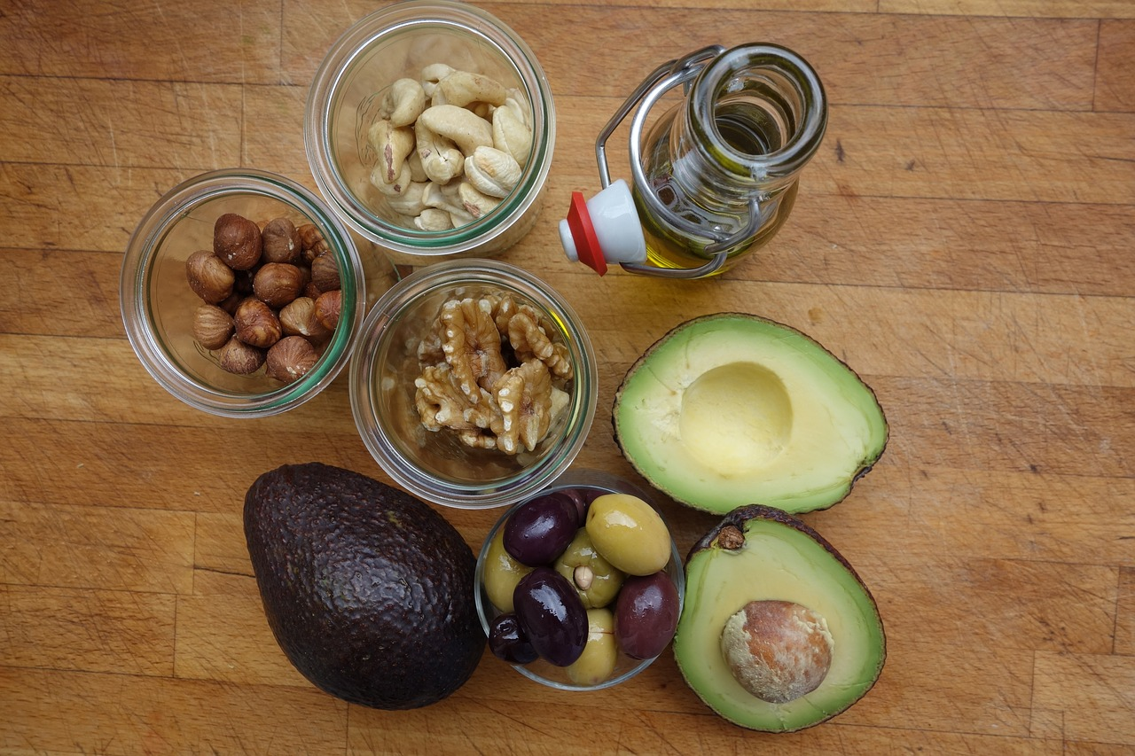overhead shot of avocados, nuts, olives and a bottle of olive oil on a wooden table