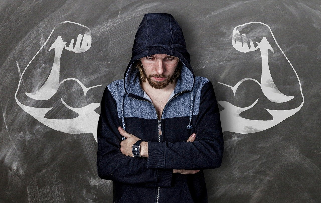 man wearing a hoodie and looking down with a chalk drawing of 2 flexed muscular arms behind him