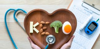 the word keto spelled out with keto-friendly foods on a wooden heart-shaped dish, with a stethoscope, medical sheet and blood glucose monitor in the background