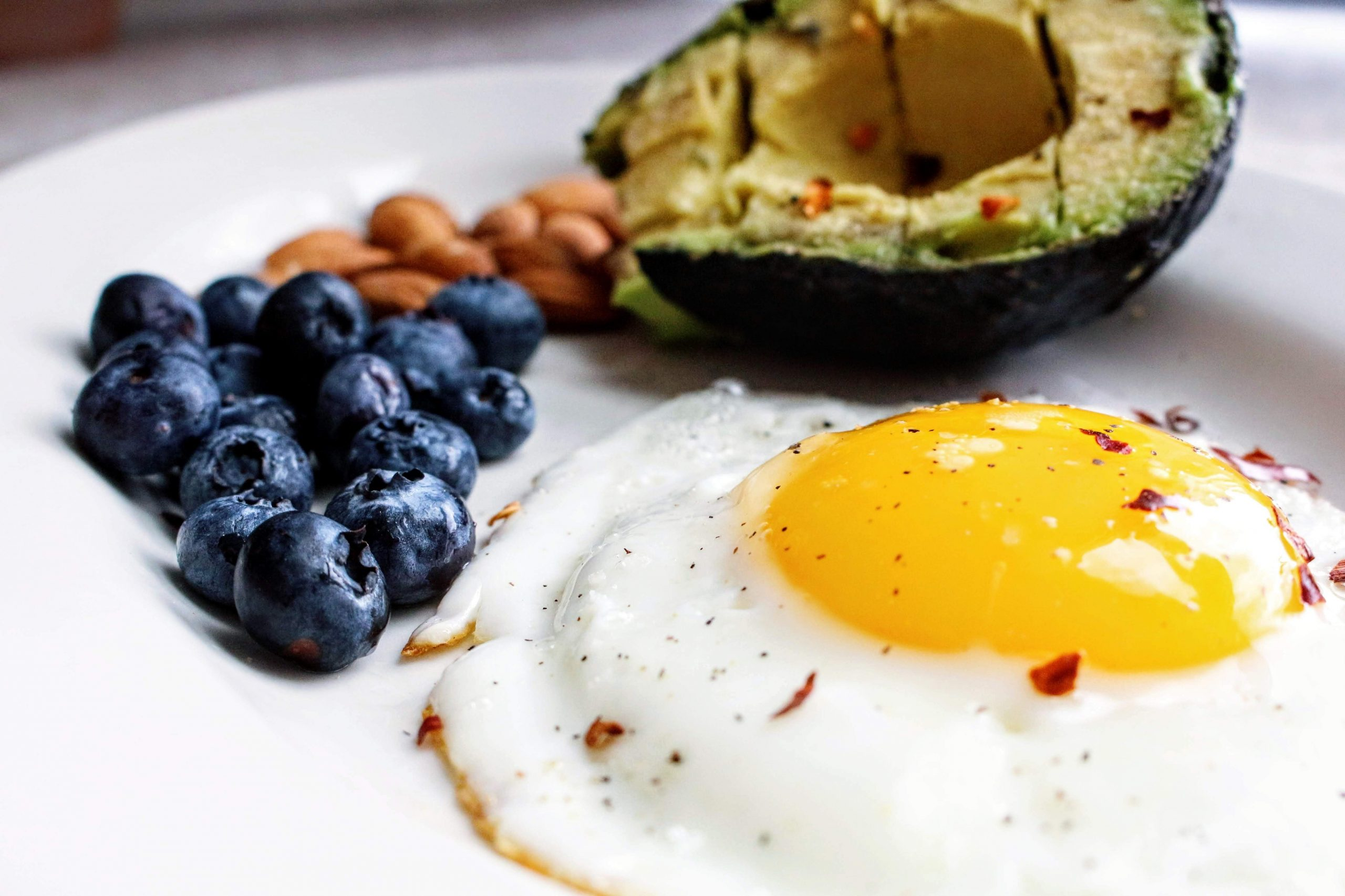white plate with a sunny-side-up, blueberries, almonds and half an avocado