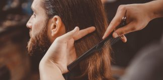 long-haired bearded man getting a haircut at the barber