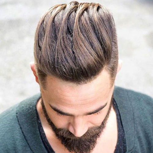 angled top view of a man's slicked back hairstyle with tapered sides