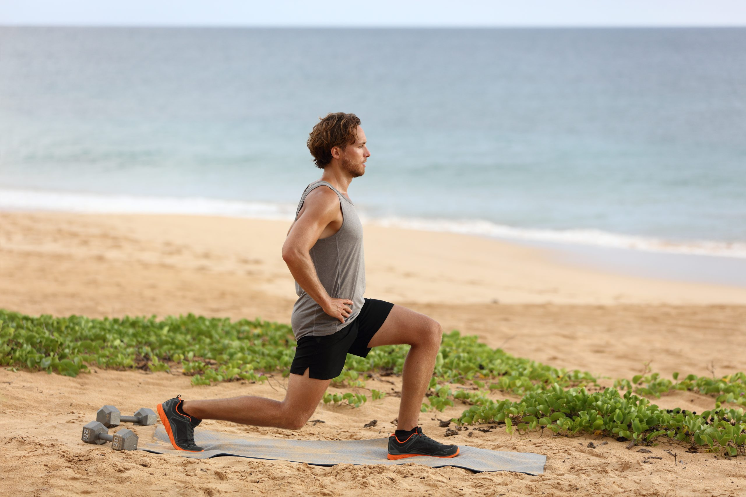 Man doing lunges near the beach