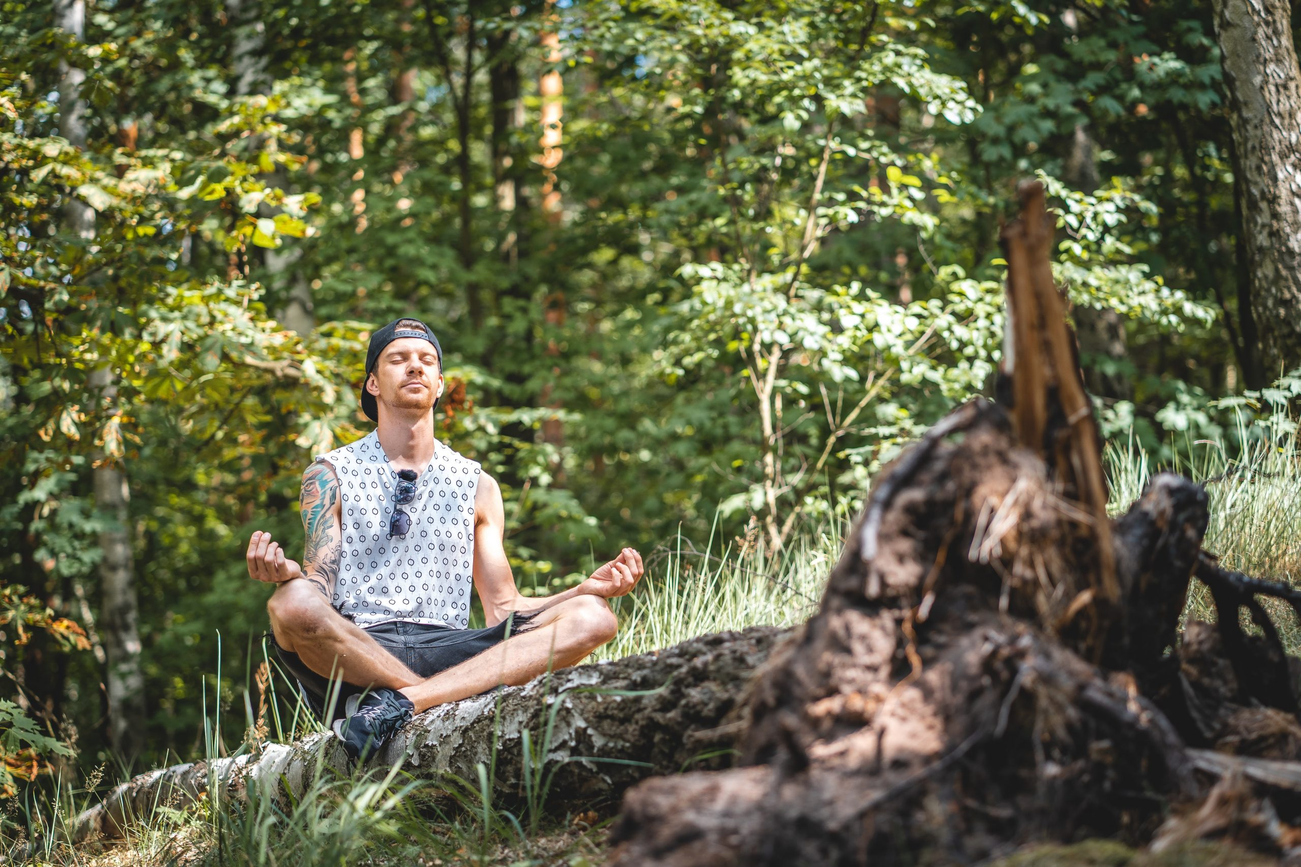 man sitting on a log in the outdoor nature meditating