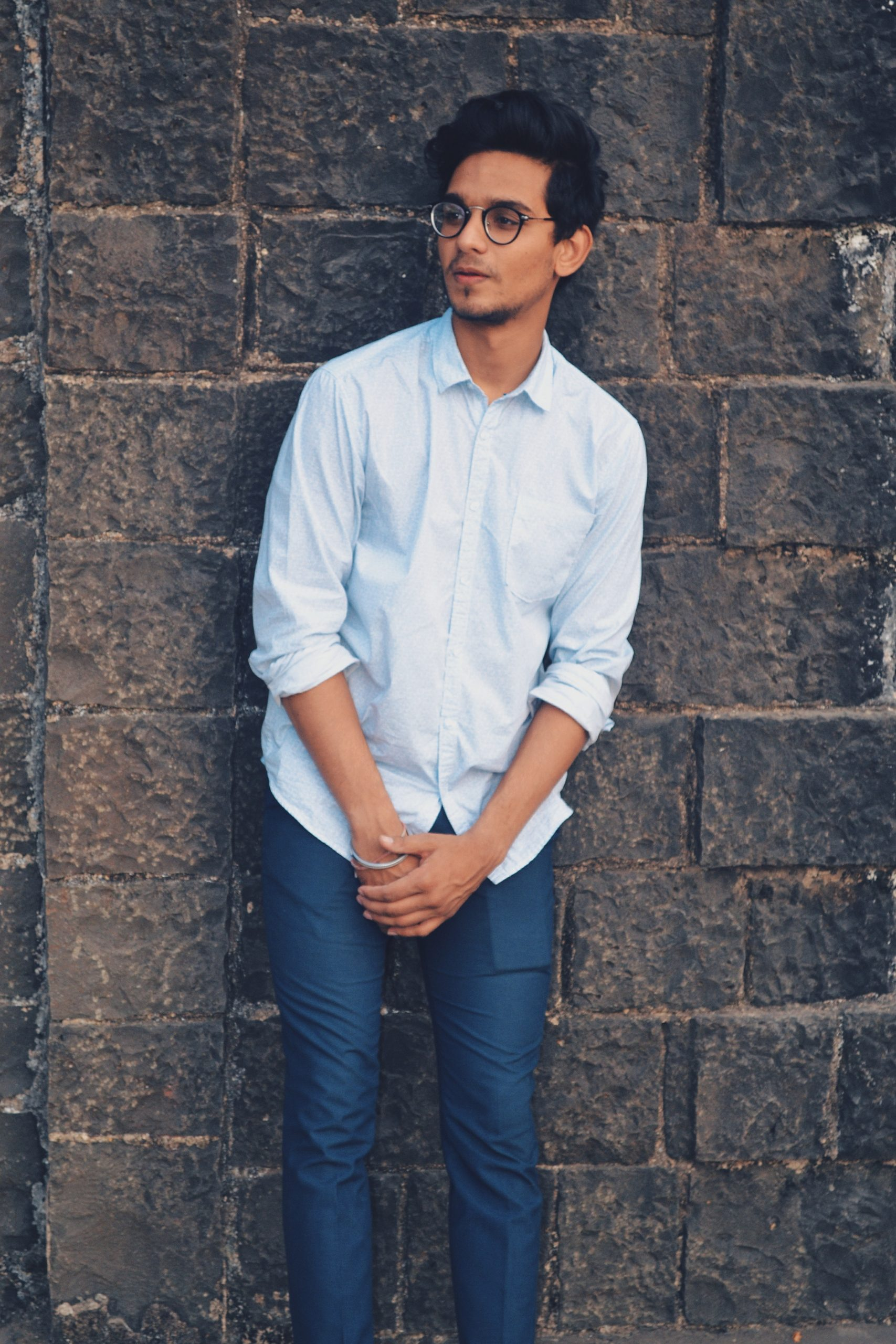 man leaning against a wall wearing a white/light blue button-up shirt and navy blue dress pants