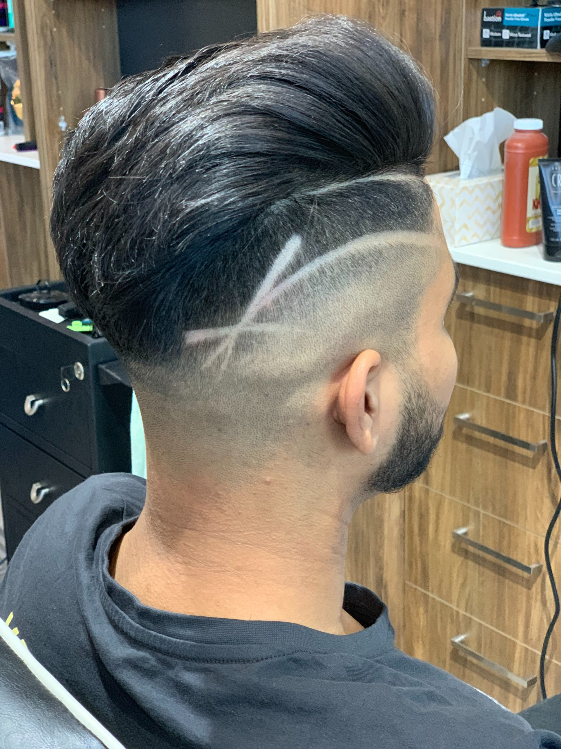 side profile of a man sitting in the barber's chair, showing off a modern pomp with a side shaved detail