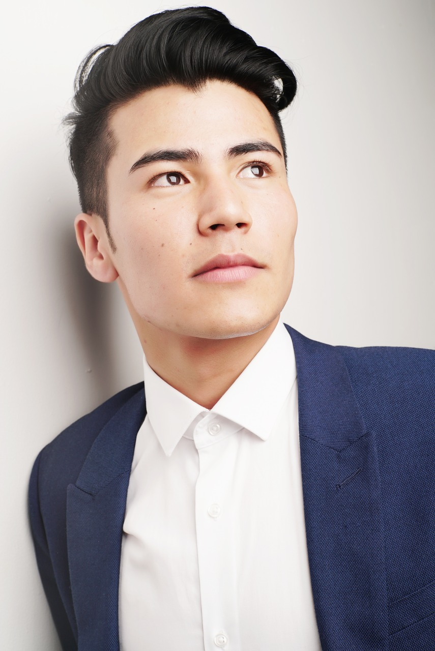asian man wearing a navy suit and looking off in the distance
