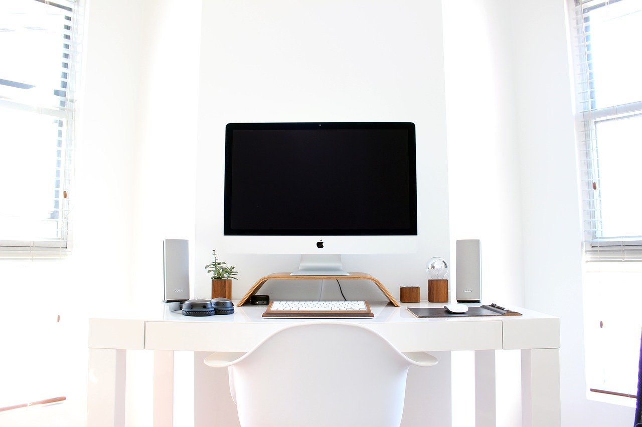 tidy work desk in a white room with an imac desktop computer, organization, tidiness, coping strategies