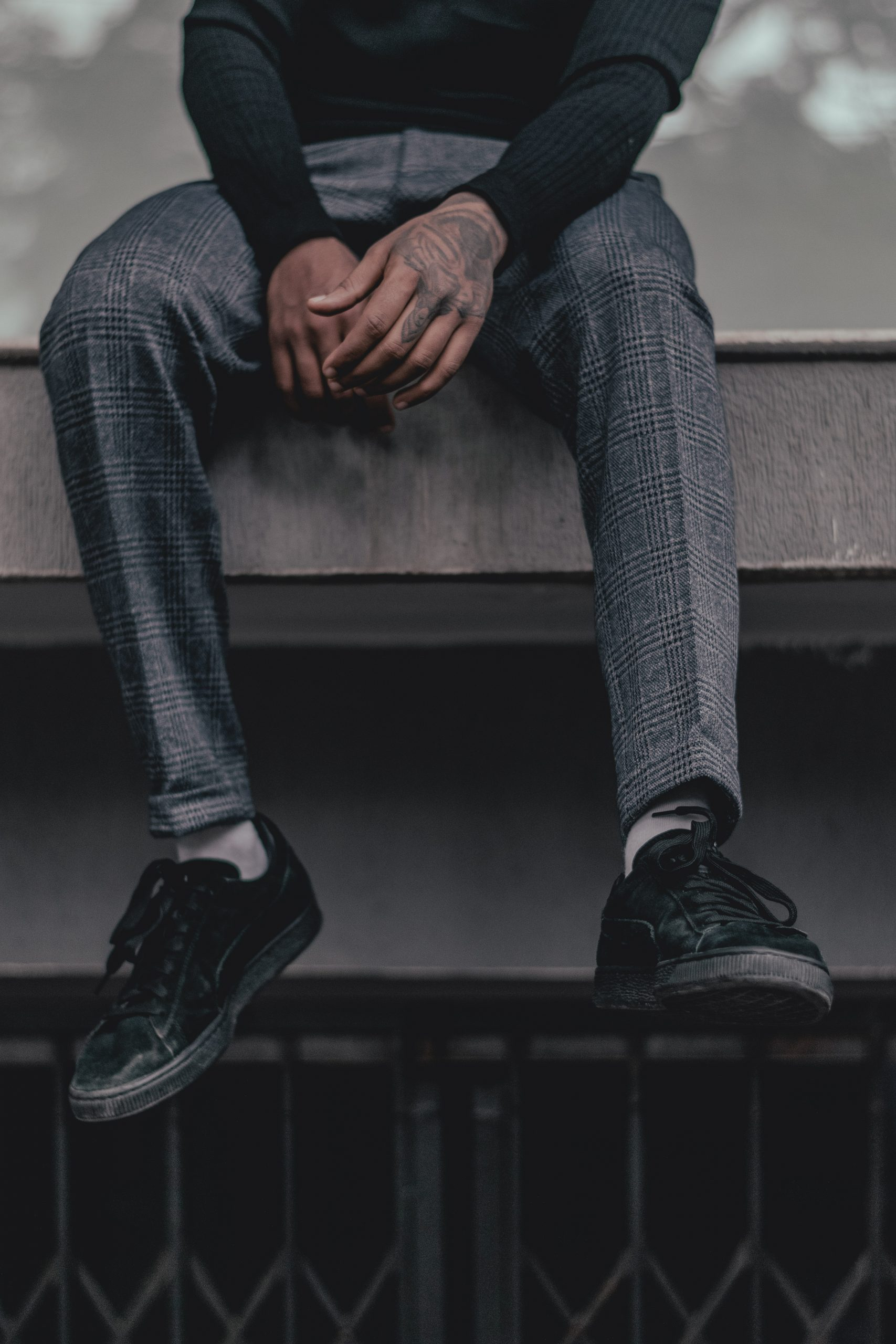 man's legs dangling from the edge of a ledge to show his checkered pants and black sneakers, business casual for men