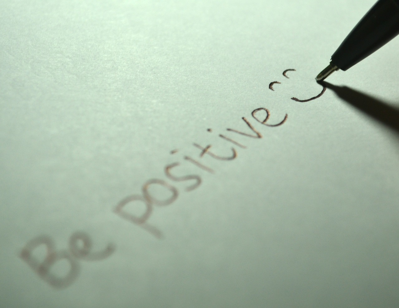 """the words """"be positive"""" and a smiling face written on a piece of paper"""
