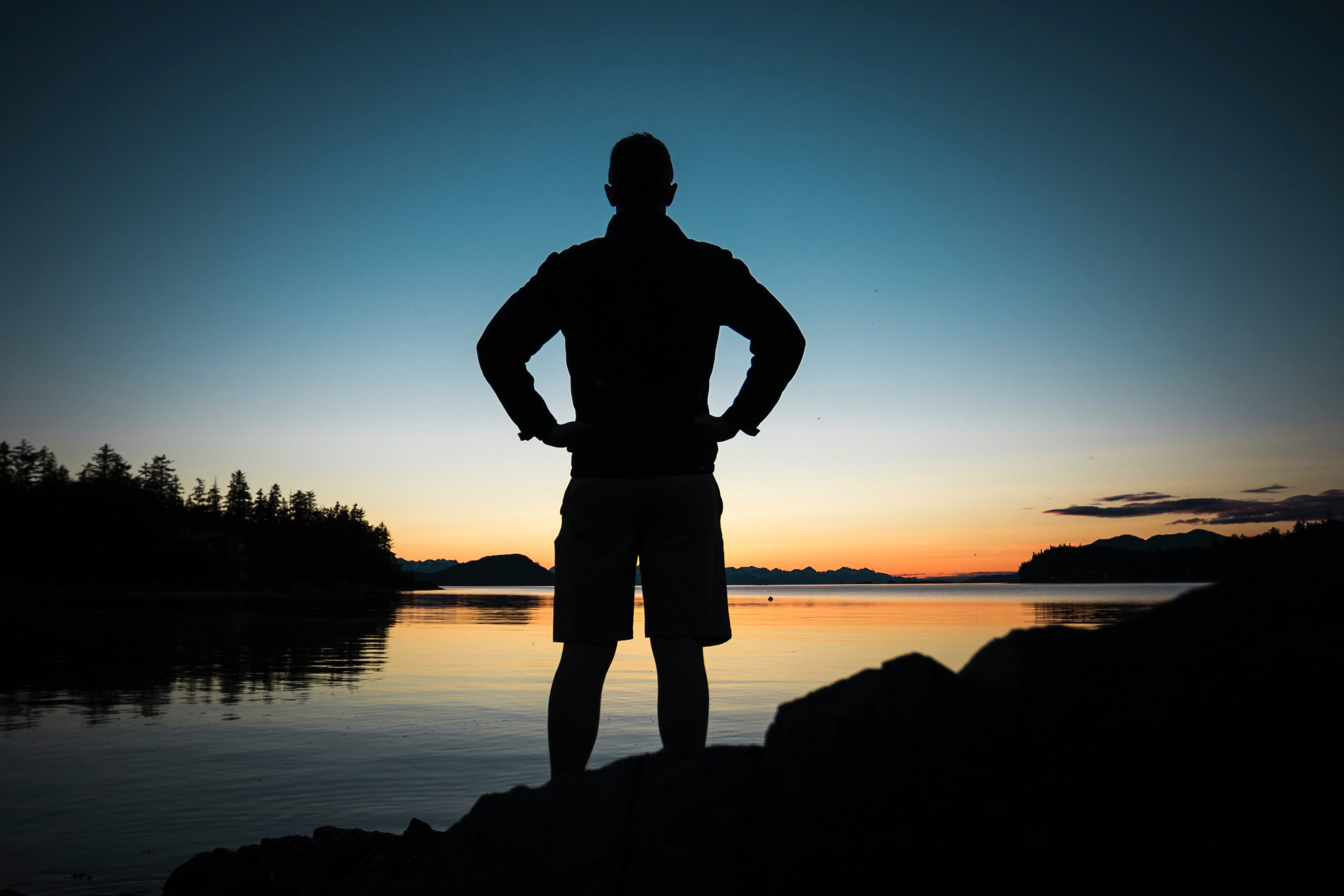 silhouette of a man near the shore looking out to the sunset, standing with his hands on his hips