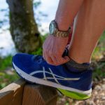 close up of a man tying his shoelaces on an outdoor forest trail