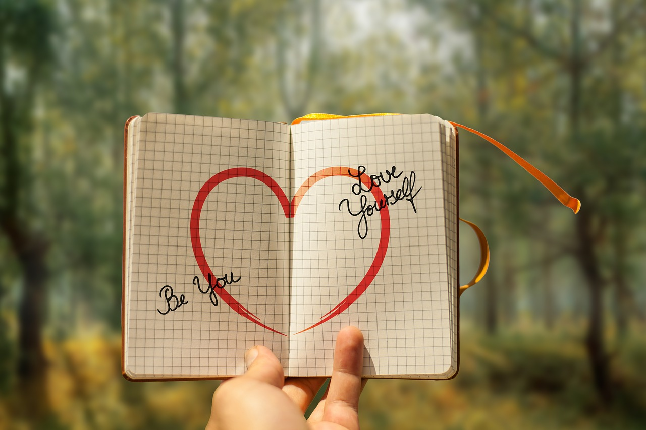 """notebook held up against a forest background, with a big red heart drawn in the middle and the words """"be you"""" and """"love yourself"""" written on it"""