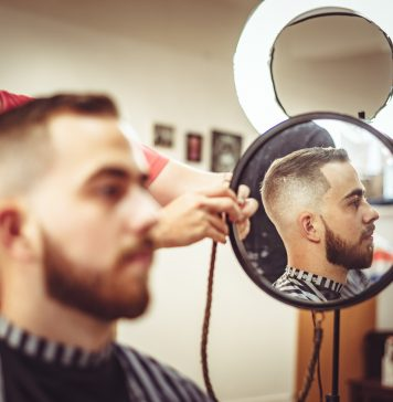 barber showing a customer his new short haircut in the mirror