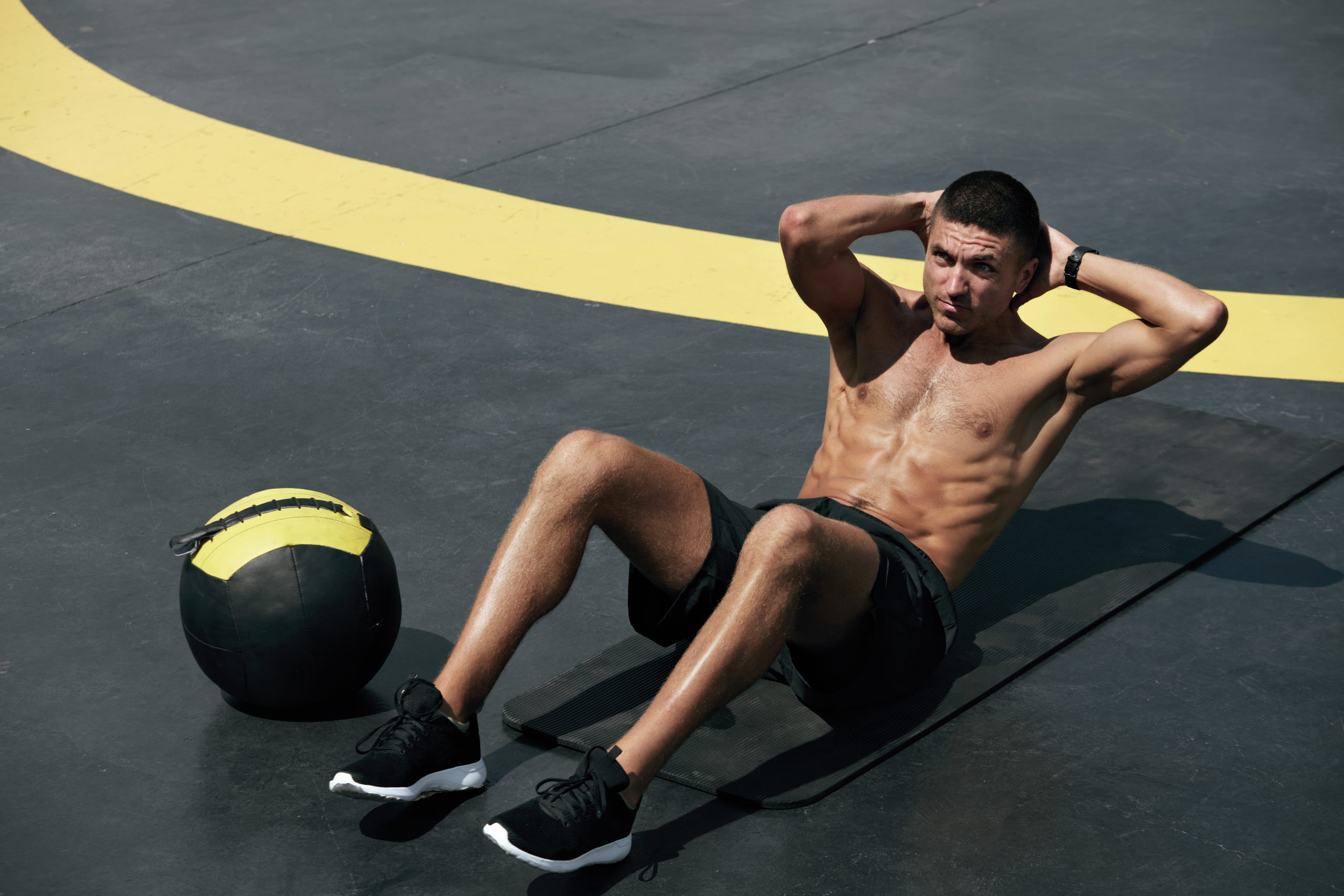 Man doing sit-ups with a black and yellow medicine ball beside him