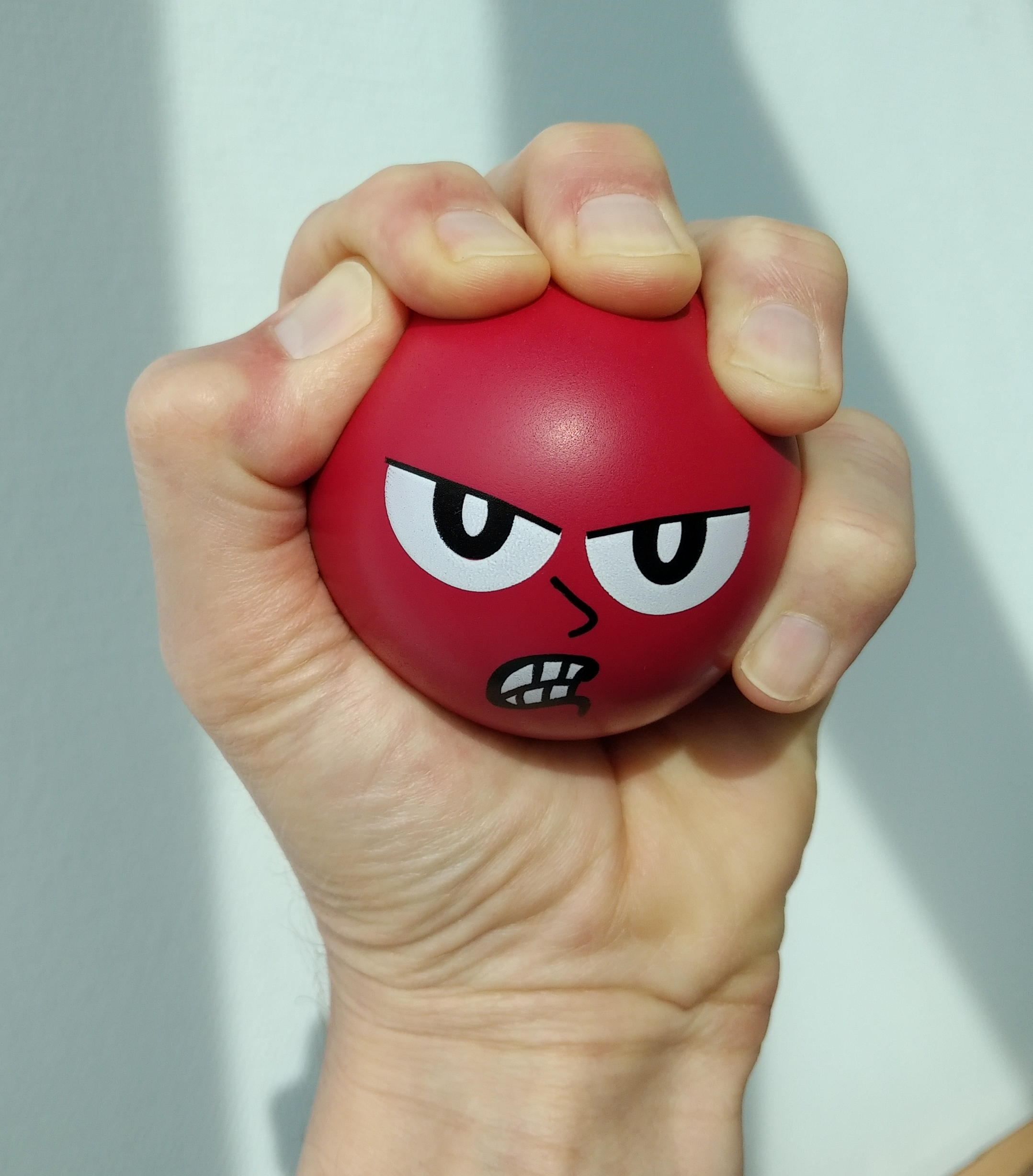 person's hand squeezing a red stress ball with an angry face on it, coping strategies, healthy coping mechanisms