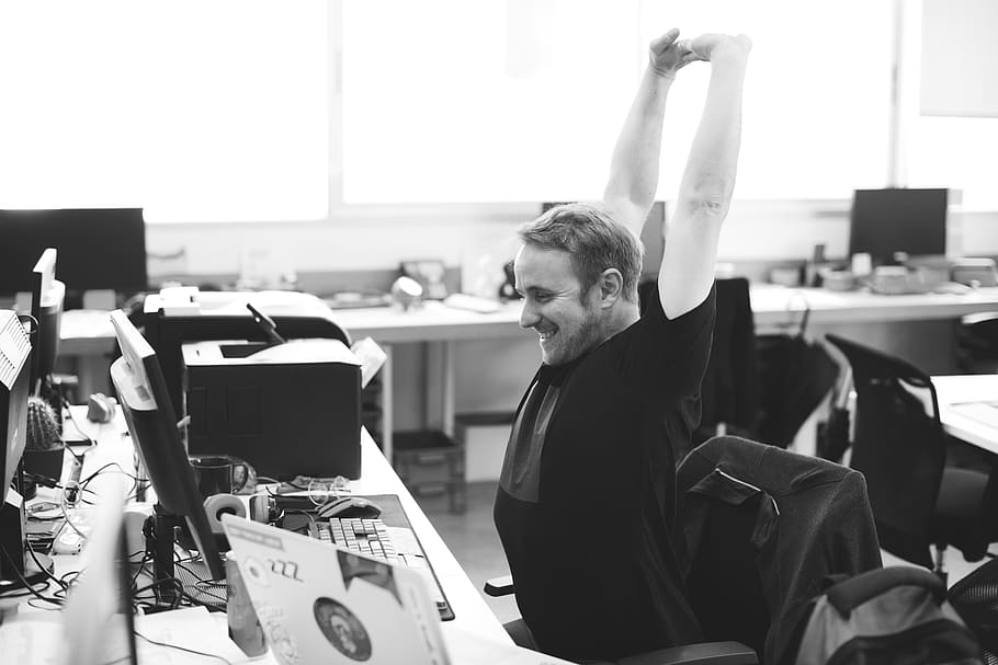 black and white shot of a man stretching his arms upwards at his office desk, stretching, take a break, coping strategies