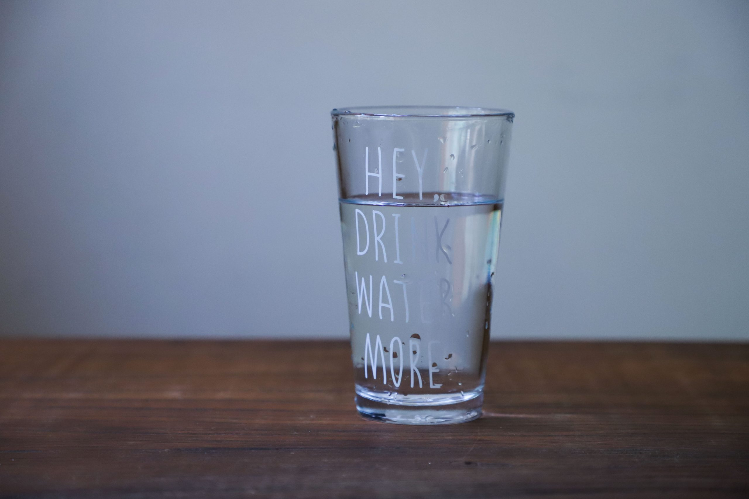 "glass of water with the words ""hey drink water more"" printed on the glass"