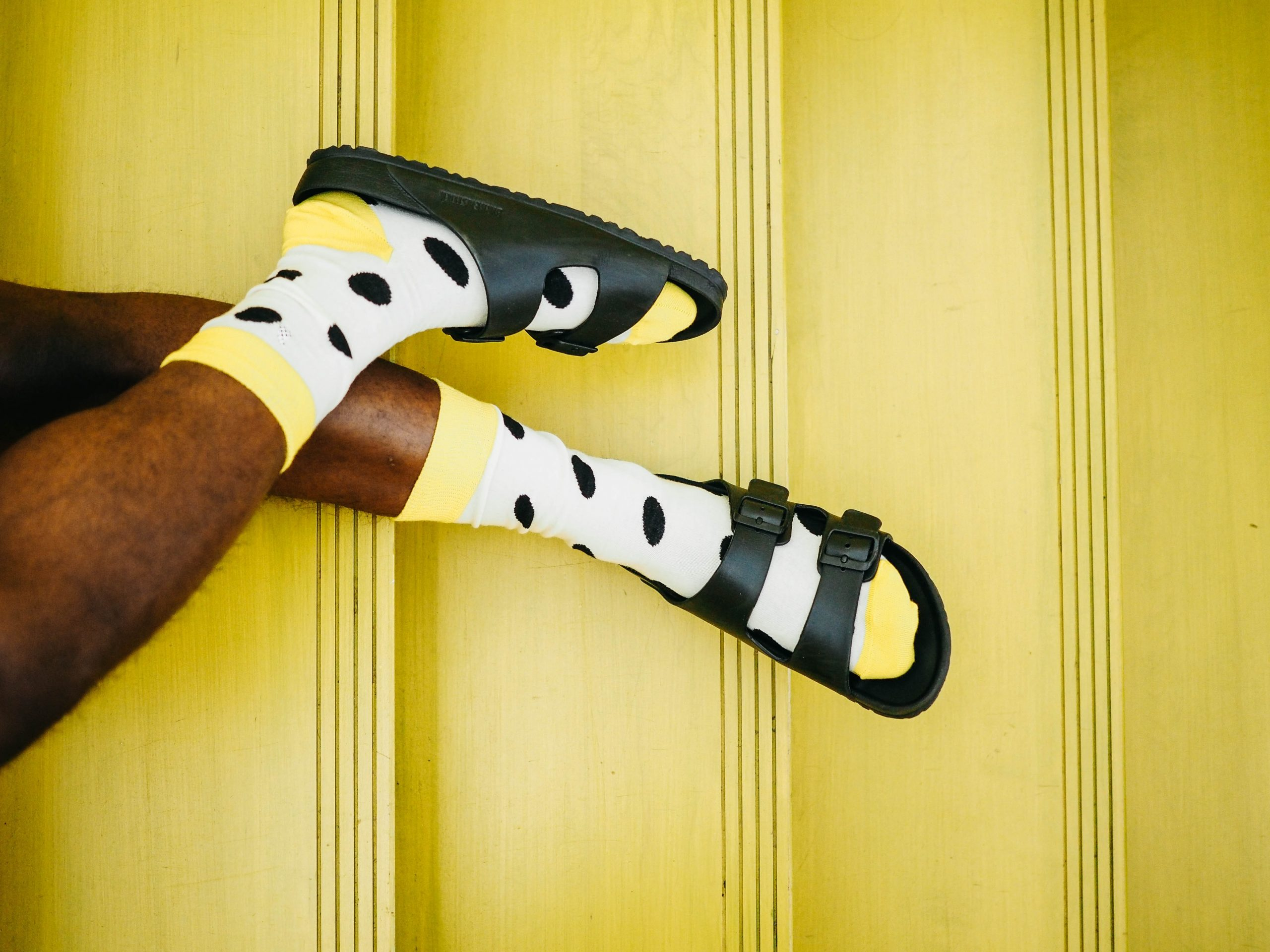 dark-skinned legs wearing white-and-yellow polka dot socks with black slides against a yellow background, casual fashion, casual outfits, casual clothes, casual wear