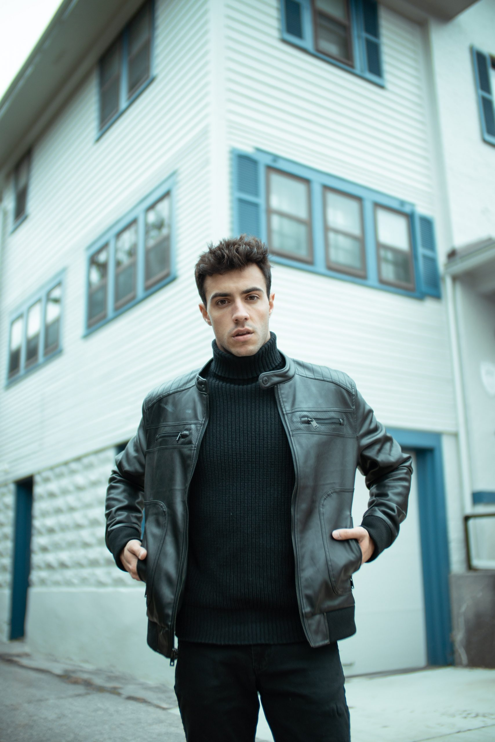 man standing in front of a building wearing a black turtleneck and black leather jacket