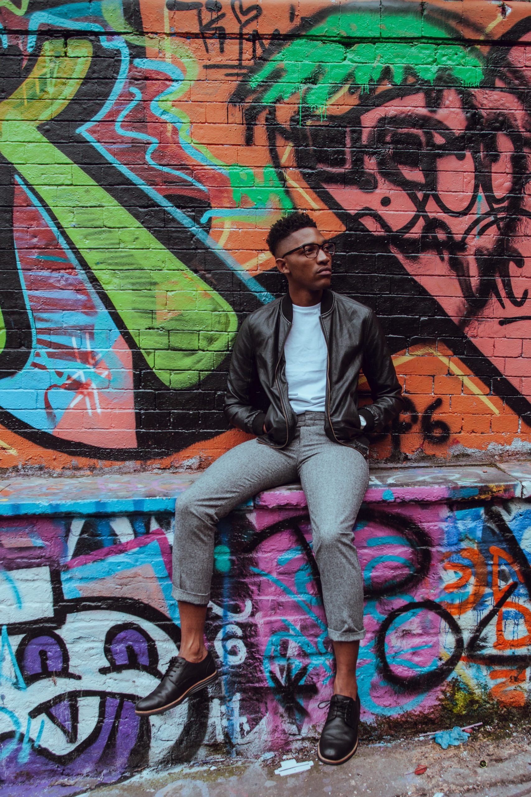 man wearing glasses, a leather jacket, white shirt and cropped pants against a graffiti wall, casual fashion, casual outfits, casual clothes, casual wear