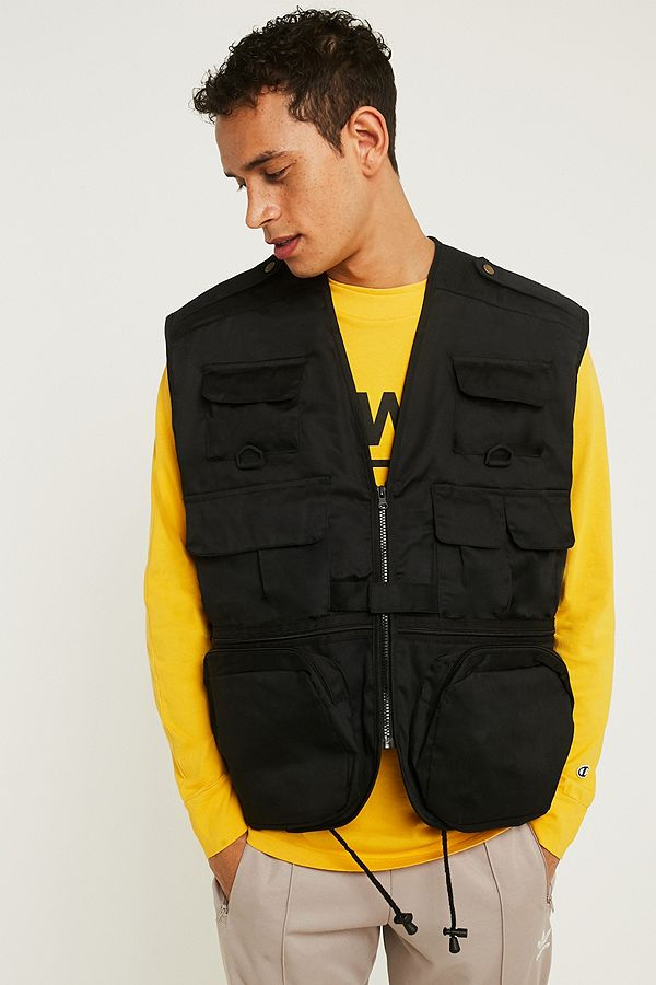 male model wearing a yellow sweatshirt and a black vest with many pockets, casual fashion, casual outfits, casual clothes, casual wear