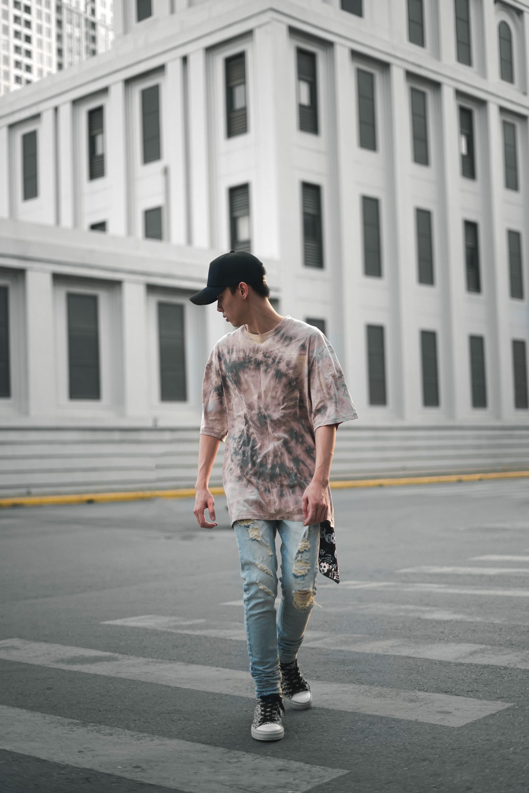 man walking across the pedestrian crossing wearing jeans, a cap and a brown-and-black tie dye shirt, casual fashion, casual outfits, casual clothes, casual wear
