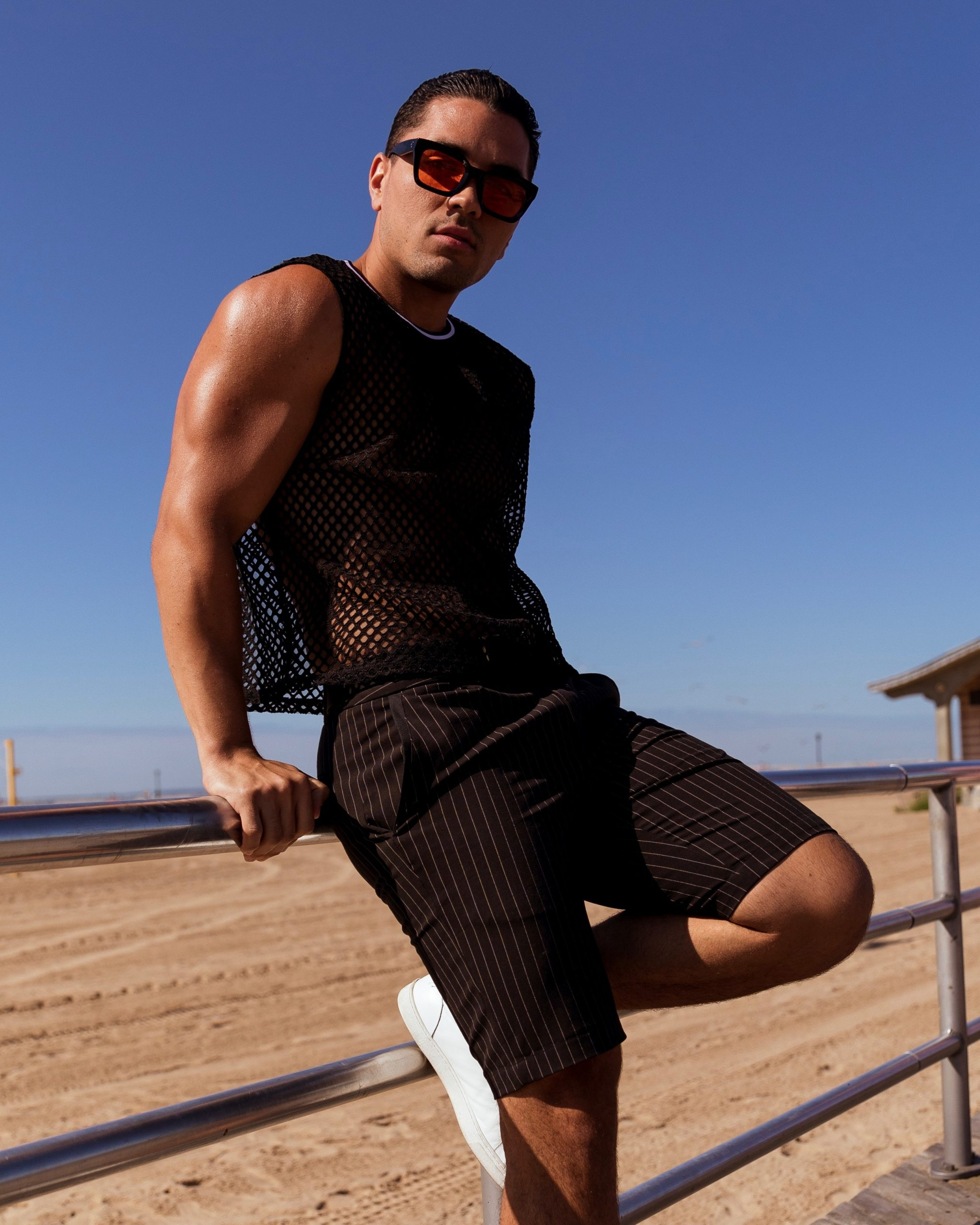 man wearing shades, a black mesh top and shorts while leaning on a railing at the beach, casual fashion, casual outfits, casual clothes, casual wear