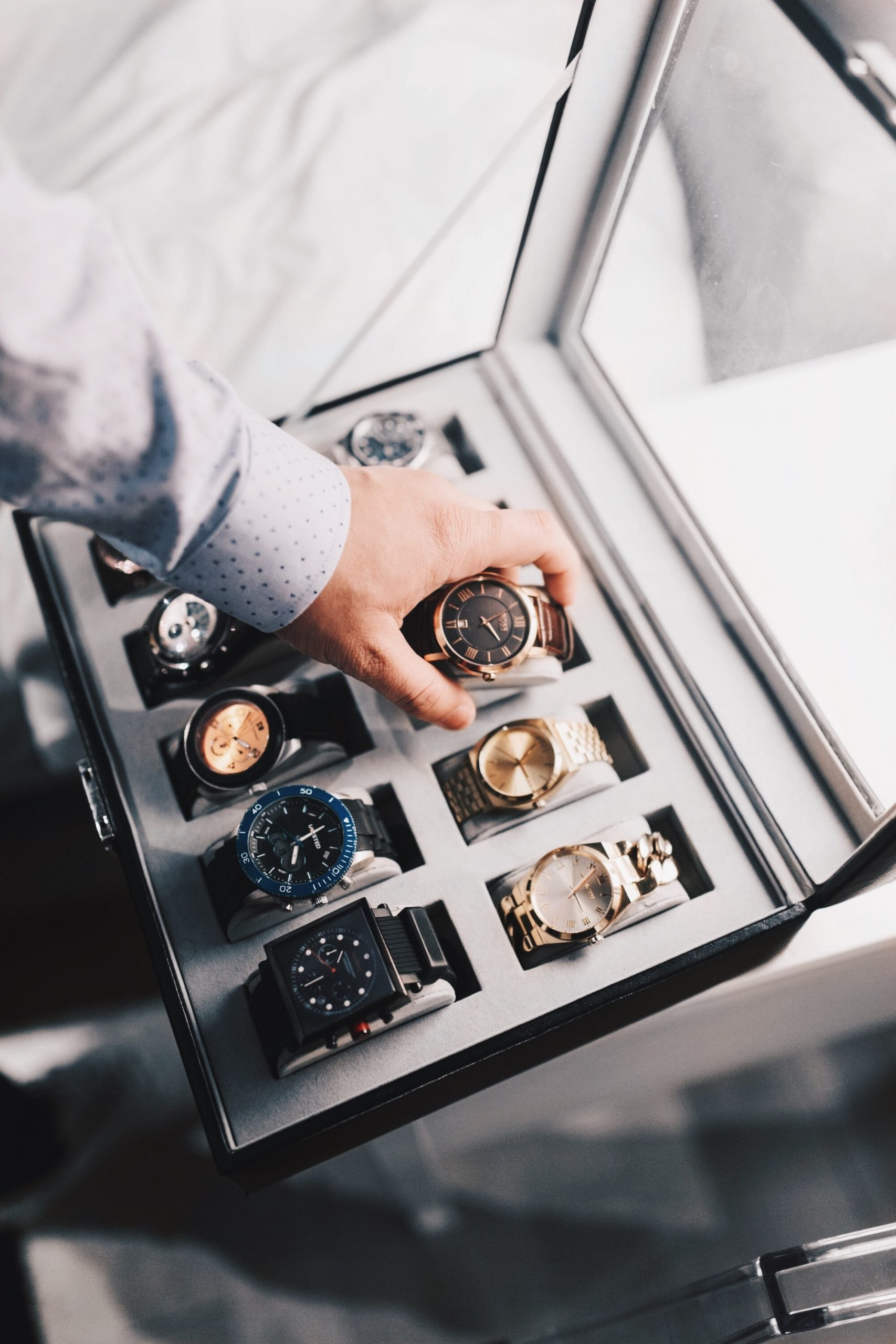 man's hand selecting a watch from his collection, wrist watch, watch selection, watch pairing, how to wear a watch