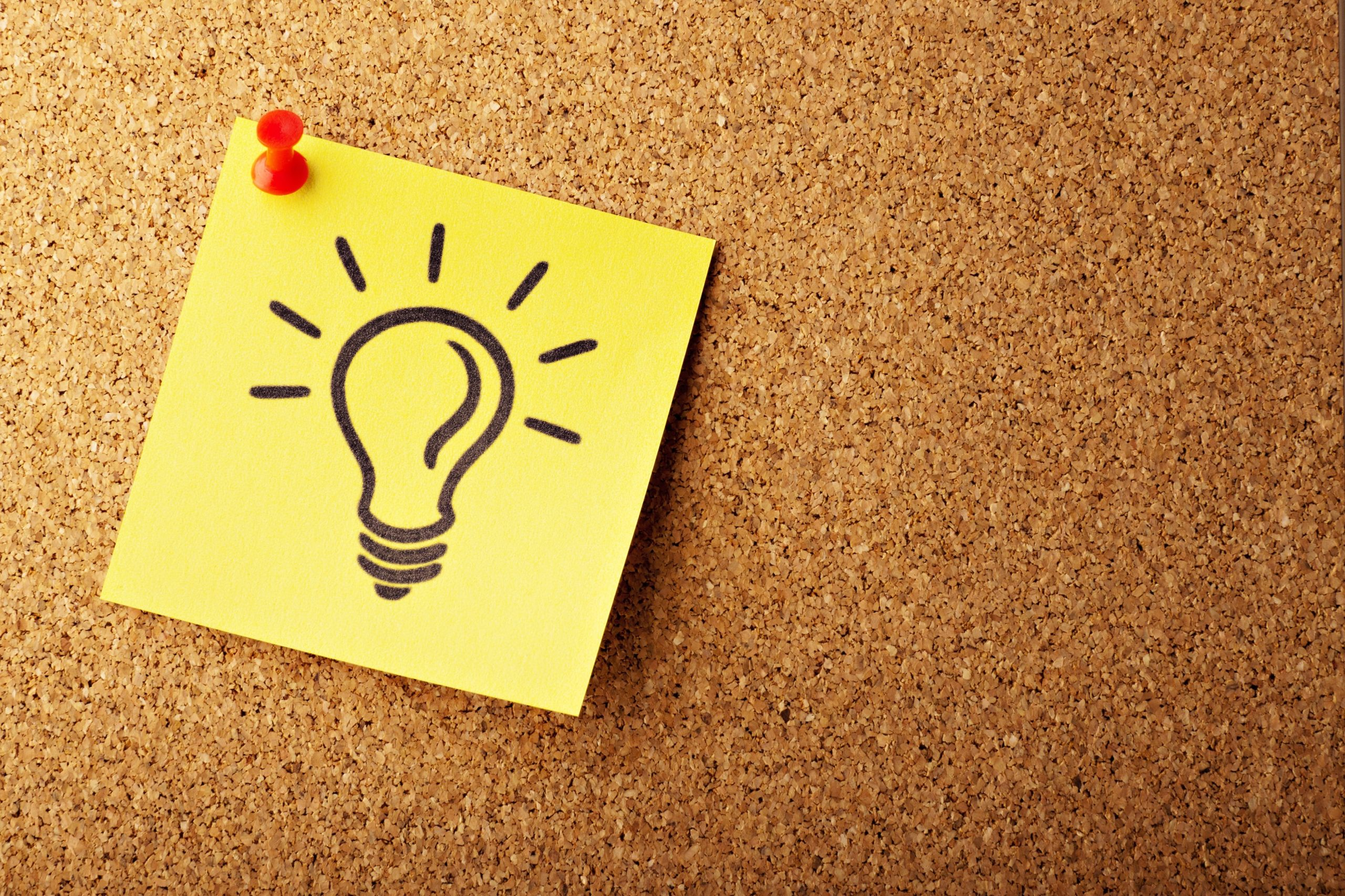 Image of a light bulb on a yellow post-it pinned to a corkboard