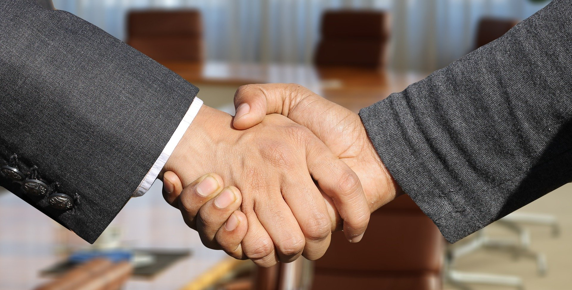 two hands in a handshake with a boardroom in the background, making a brand promise