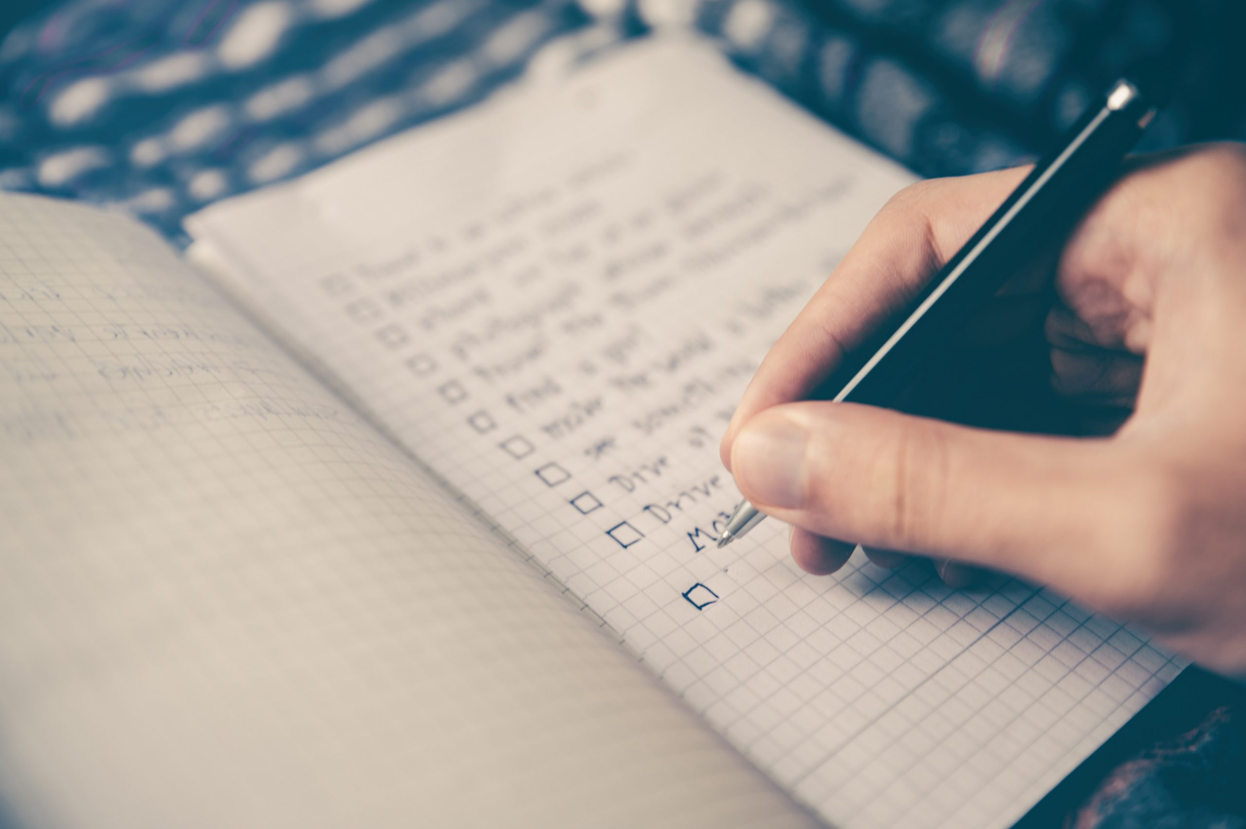 person's hand writing a checklist on a notebook