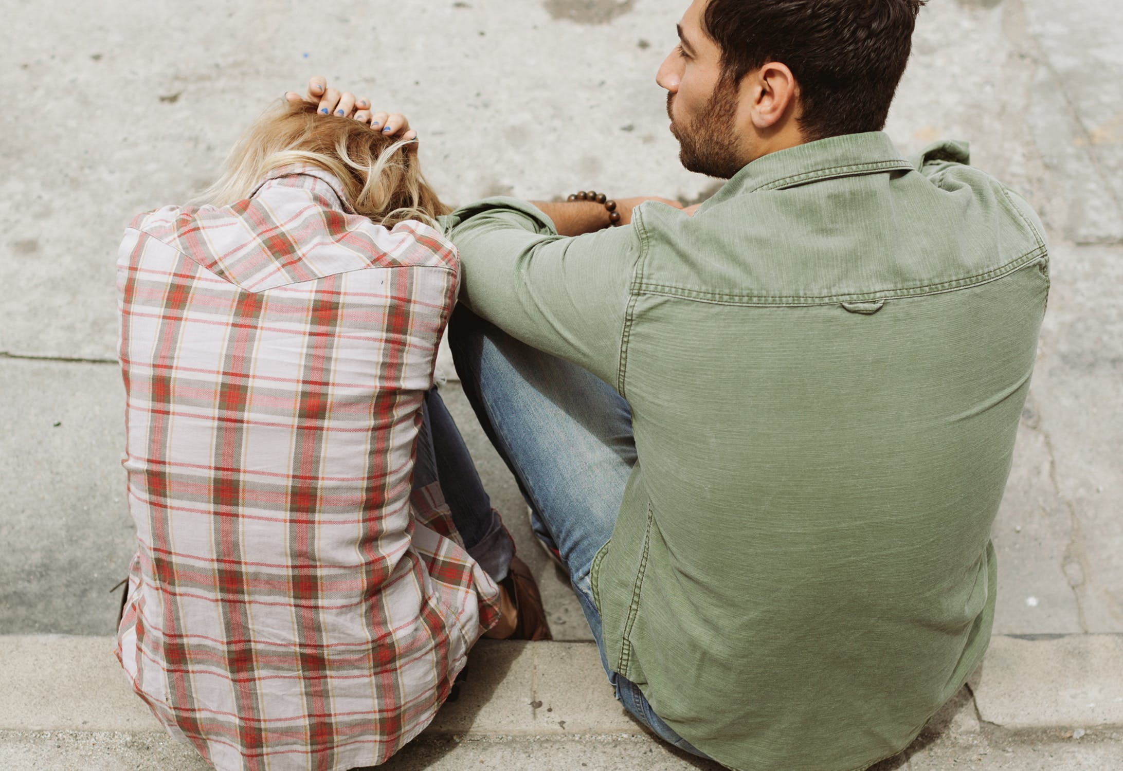 couple sitting on the sidewalk with the woman having her head down, argument, disagreements, breakups