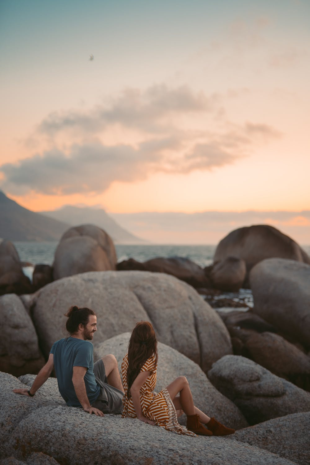 couple smiling while sitting on rocks near the seaside, happy times, couple, relationship