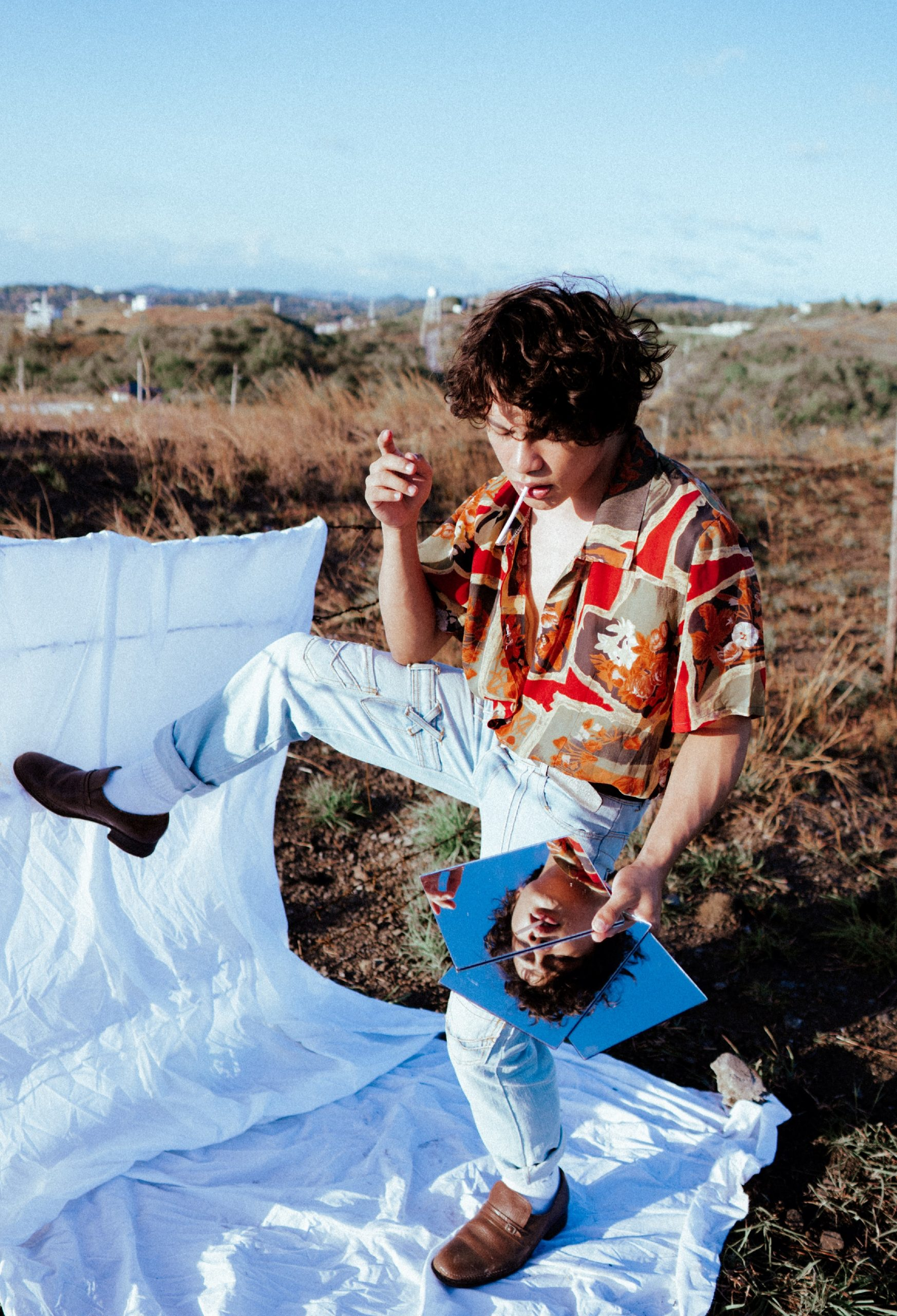 man with colorful box shirt and jeans posing on a white sheet on an open field, casual fashion, casual outfits, casual clothes, casual wear