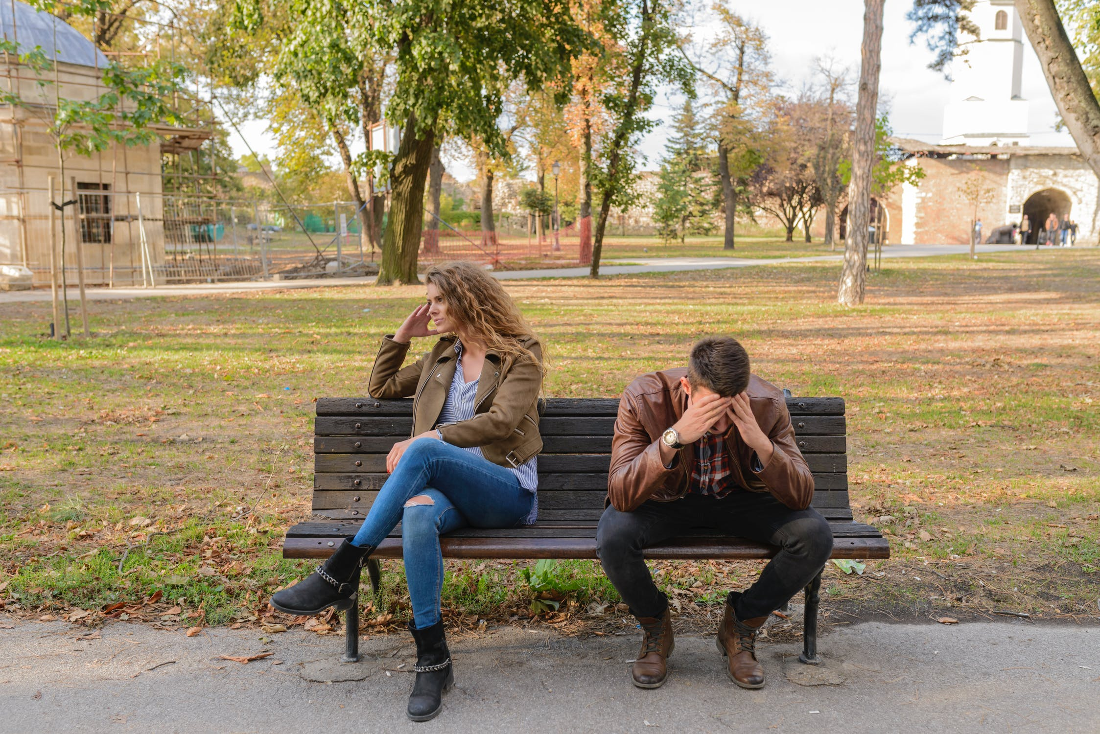 angry couple sitting on a park bench after an argument, quarrel, disagreements, breakups