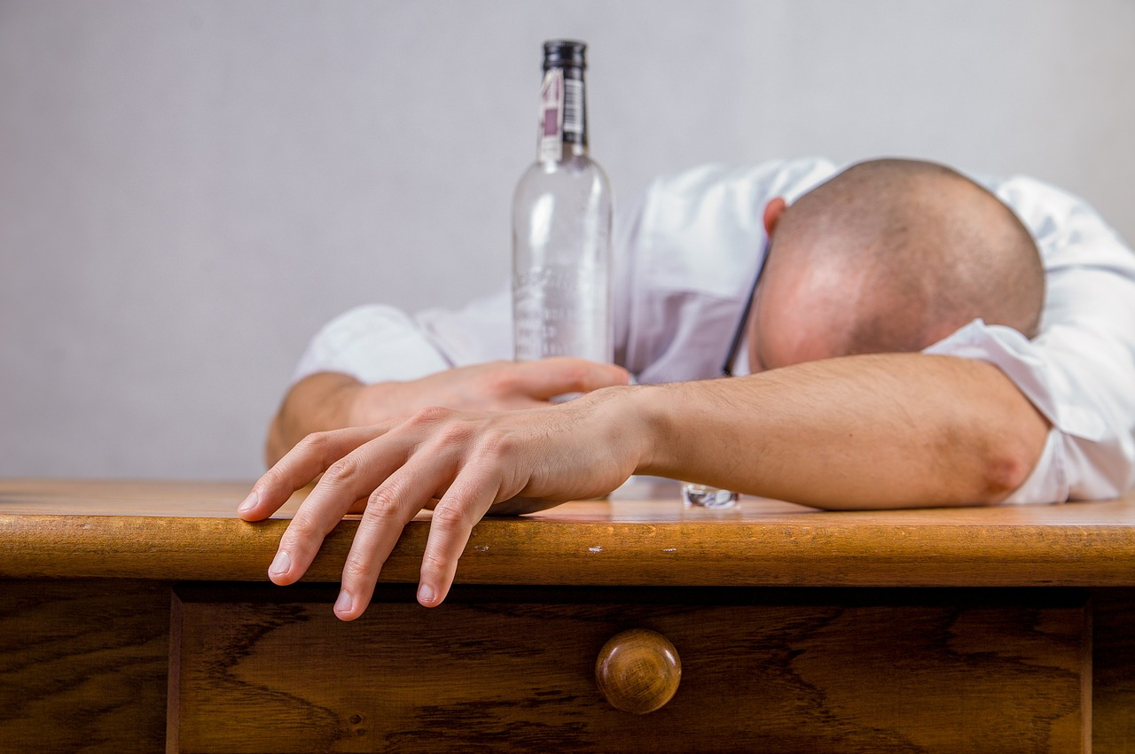 man with his head down on a table and having an empty bottle of alcohol, hungover