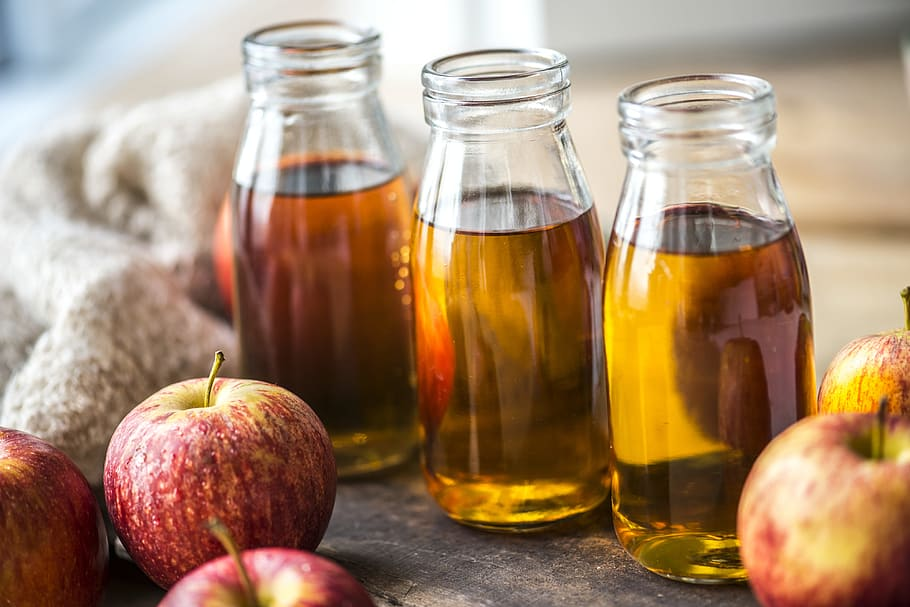 three glass bottles of apple cider vinegar with apples and a warm sweater around them, homemade conditioner ingredients