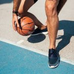 man's basketball shoes as he dribbles a basketball