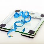 glass weighing scale with a blue measuring tape on it