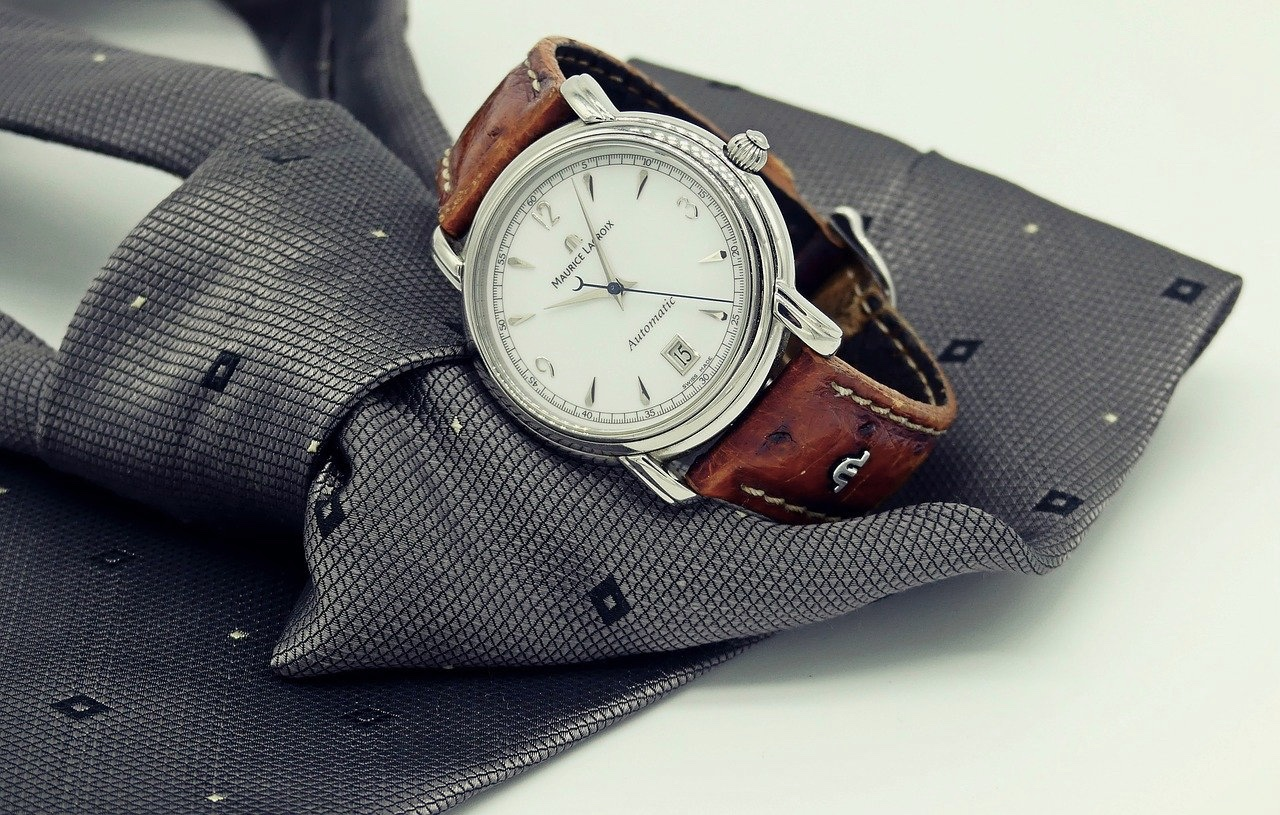 wristwatch placed on a gray necktie, business casual for men