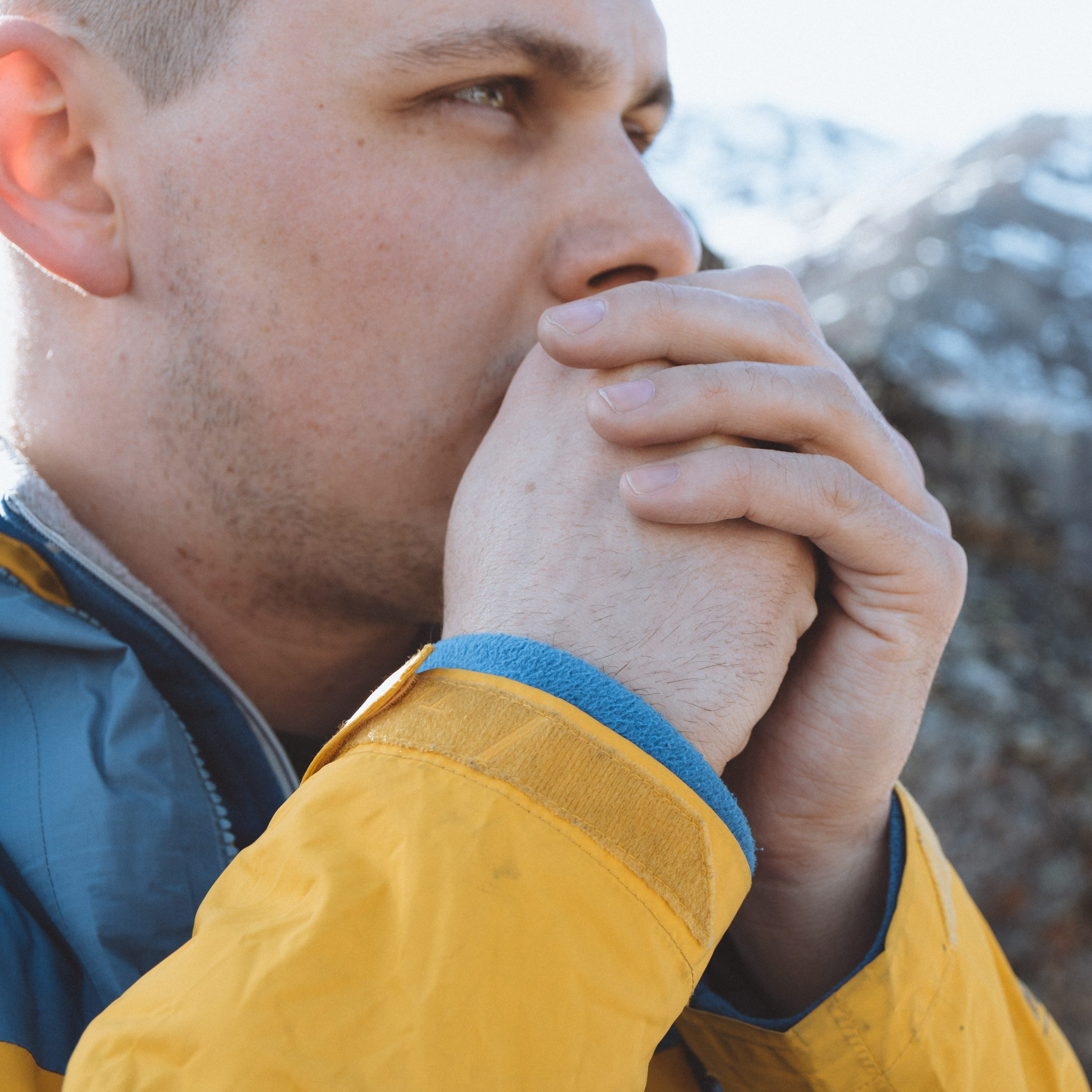 man warming his hands with his breath, cold hands, warmth