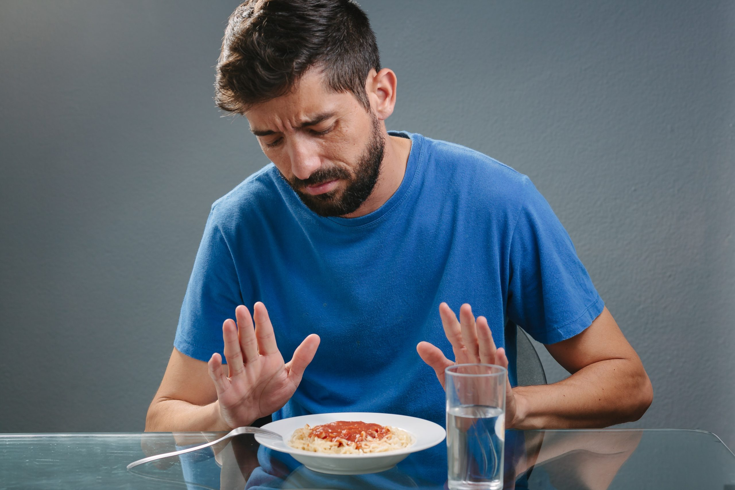man wearing a blue shirt pushing away his plate of spaghetti, loss of appetite, eating disorder, intermittent fasting