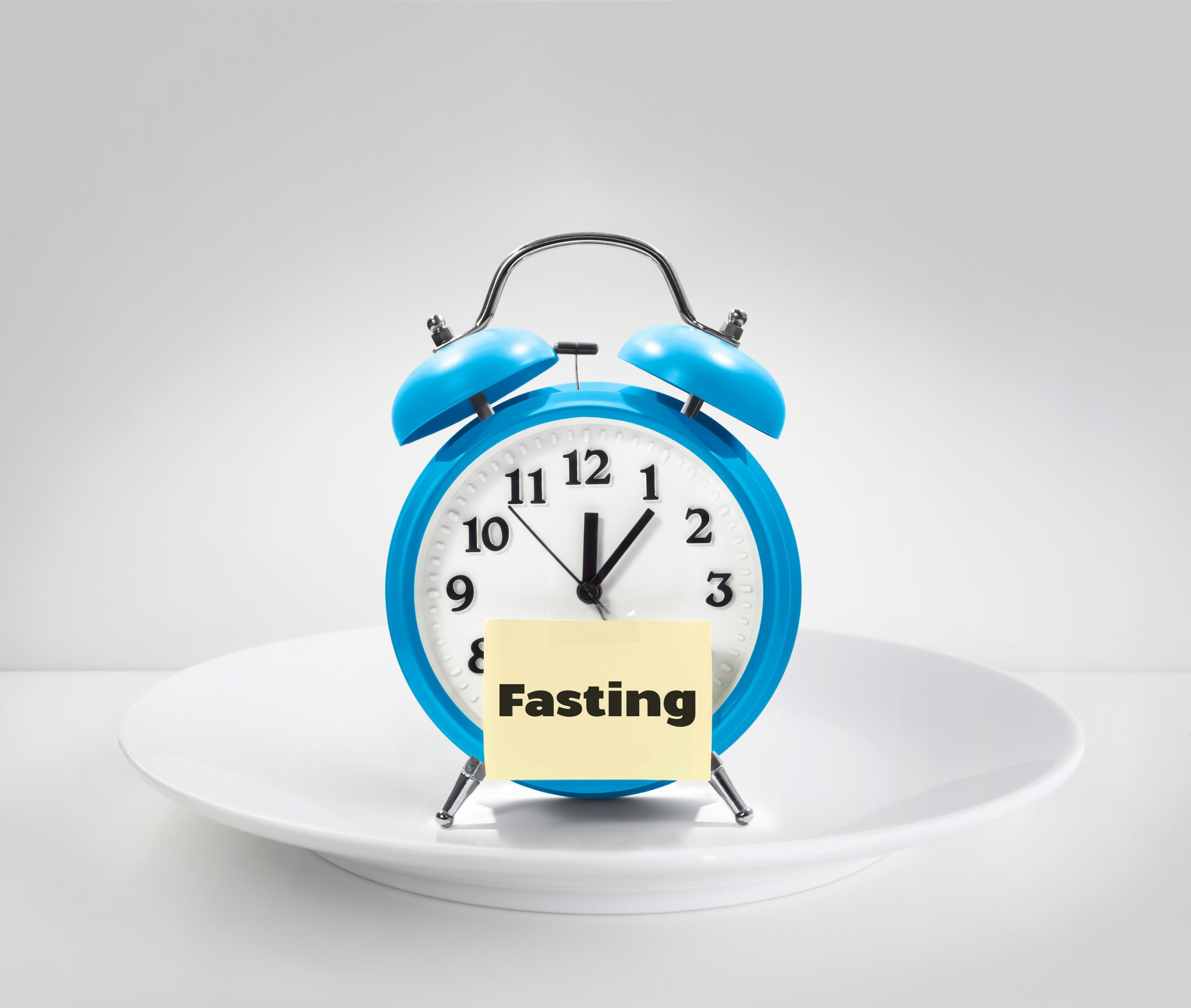 "blue alarm clock with a yellow post with the word ""fasting"" written on it placed on a white plate, intermittent fasting, fasting time, periodical fasting"